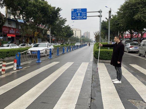 佟勤力手举盲杖,示意他要过马路。