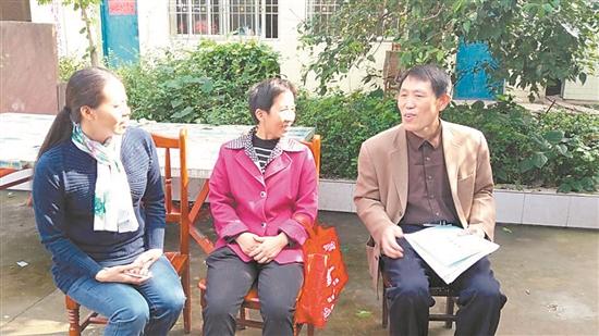 贺仲华(右)向村民宣传柑桔管理技术。